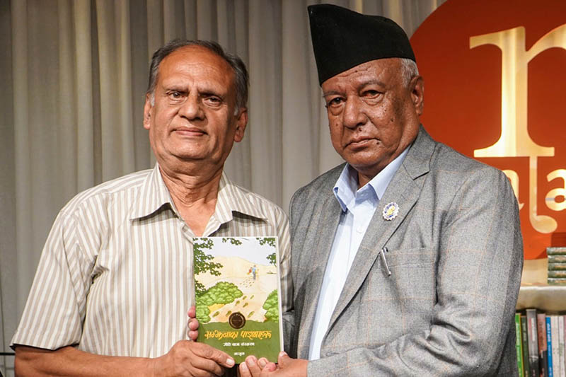 Poet Manjul hands over his book to his old colleague and lyricist Niran. Courtesy: Nepalaya