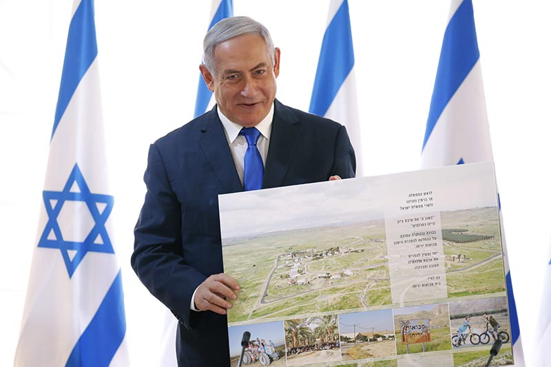 Israeli Prime Minister Benjamin Netanyahu holds up a placard given to him as a gift from Israeli residents of the area, at the start of a weekly cabinet meeting being held in a makeshift tent in the Jordan Valley, in the Israeli-occupied West Bank, Sunday, on September 15, 2019. Photo: AP