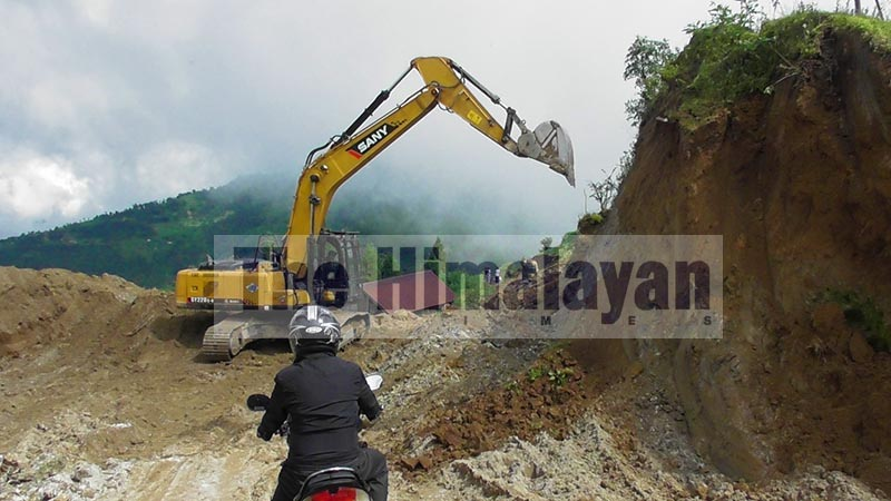 A motorcyclist rides down the road as an excavator removes earth from roadside hill along Ranke-Rabi road section, at Gumbadanda in Limba, Miklajung Rural Municipality-7, Panchthar, on Friday, September 13, 2019. The 80-km under construction road links Limba and Durdimba with Phidim, Panchthar district headquarters. Photo: Laxmi Gautam/THT