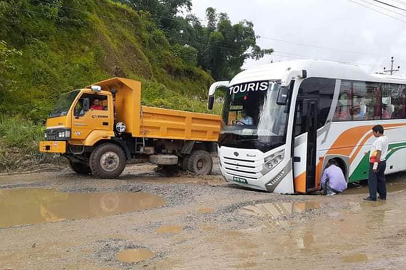 A tourist bus is stuck in a pothole as a truck wades through waterlogged puddles along Damauli--Khairenitar road stretch of the Prithvi Highway, in Tanahun district, on Monday, September 09, 2019. Photo: Madan Wagle/THT