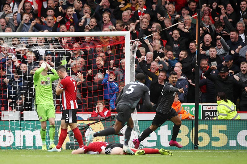 Liverpool's Georginio Wijnaldum celebrates scoring their first goal with Roberto Firmino as Sheffield United's Dean Henderson and team mates look dejected during the Premier League match between Sheffield United and Liverpool, at Bramall Lane, in Sheffield, Britain, on September 28, 2019. Photo: Action Images via Reuters