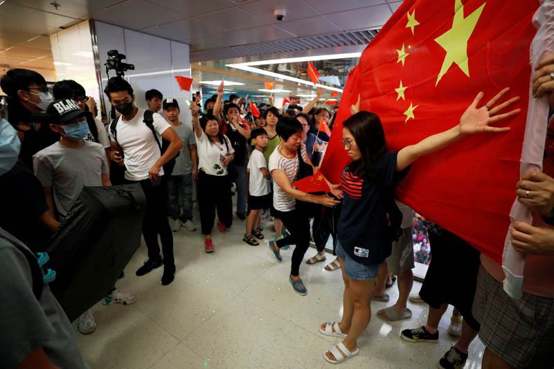 A Pro-China demonstrator stands in front a Chinese national flag during an argument with anti-government protesters at Amoy Plaza shopping mall in Kowloon Bay, Hong Kong, China, September 14, 2019. Photo: Reuters