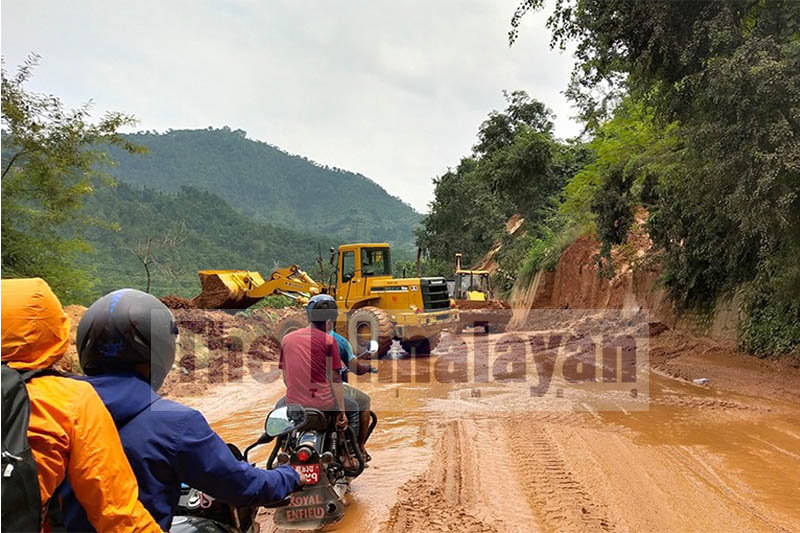 Motorcyclists wait as dozers clear mudslide debris near Galchhi Bazaar along the Prithvi Highway, in Dhading district, on Wednesday, September 11, 2019. Photo: Keshav Adhikari/THT