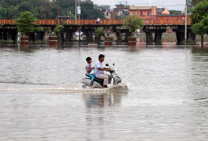 A man and a boy ride a scooter through a flooded road after heavy rains in Prayagraj, India, September 29, 2019. Photo: Reuters