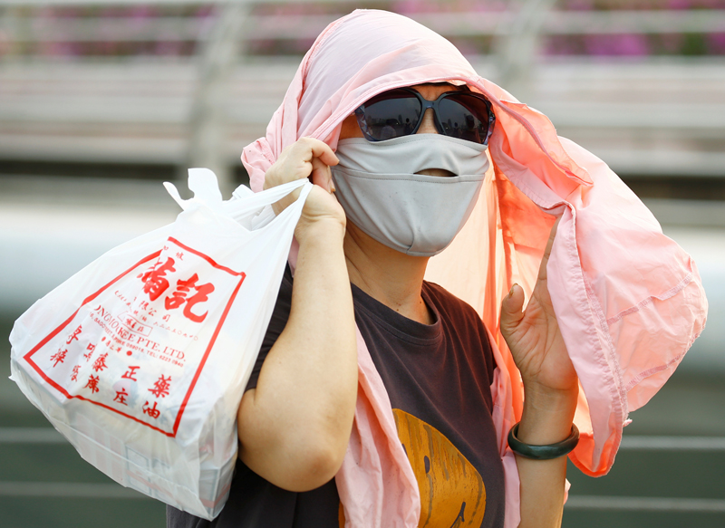 A tourist wearing a mask to protect against the haze is seen in Singapore September 13, 2019. Photo: Reuters