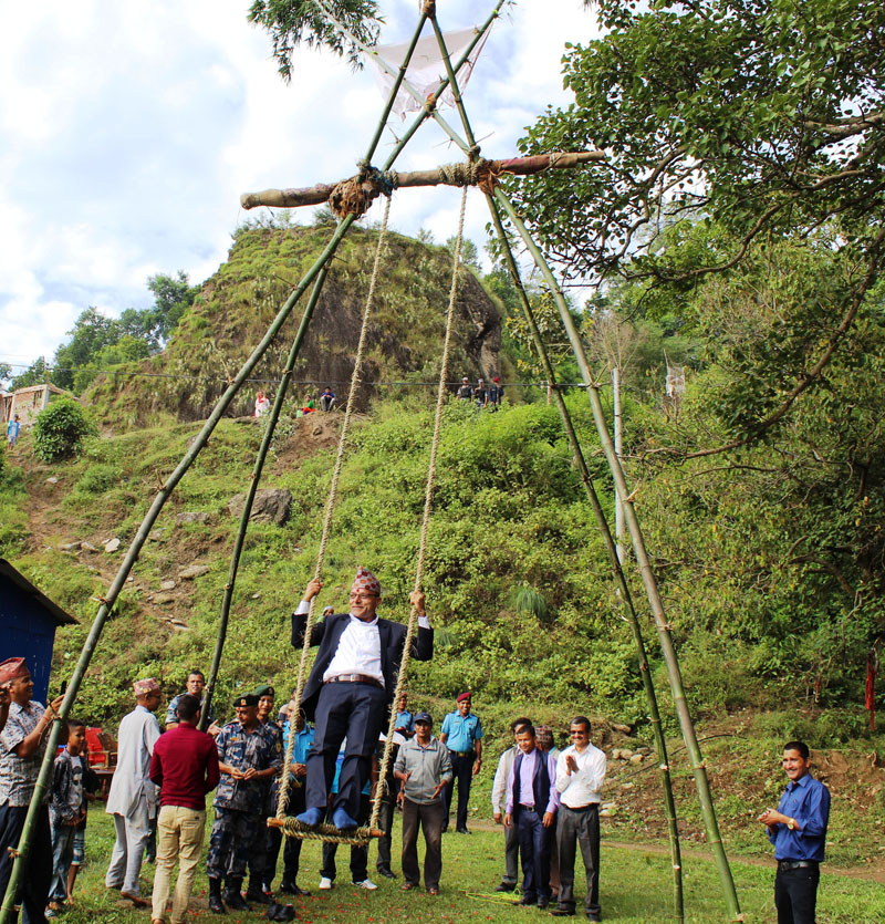 Chief District Officer of Doti, Tek Narayan Paudel, playing traditional Linge Ping (Bamboo swing) at Bedukhole, Dipayal in Doti district on Wednesday, October 2, 2019. The ping was constructed by 36 Number Battalion of Armed Police Force of Nepal. Photo: RSS