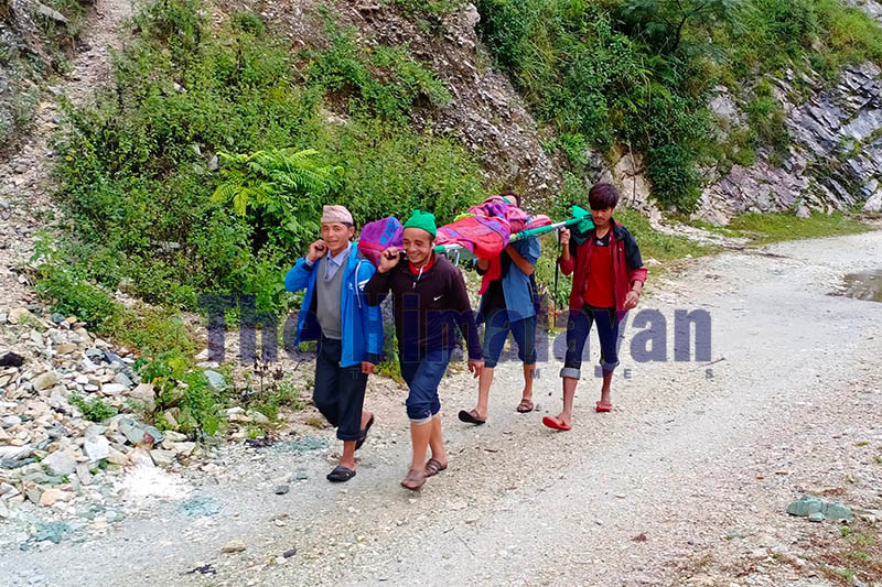 Villagers carrying a patient on a strecther to a nearby hospital in Bajura district, on Thursday, October 31, 2019. Photo: Prakash Singh/THT