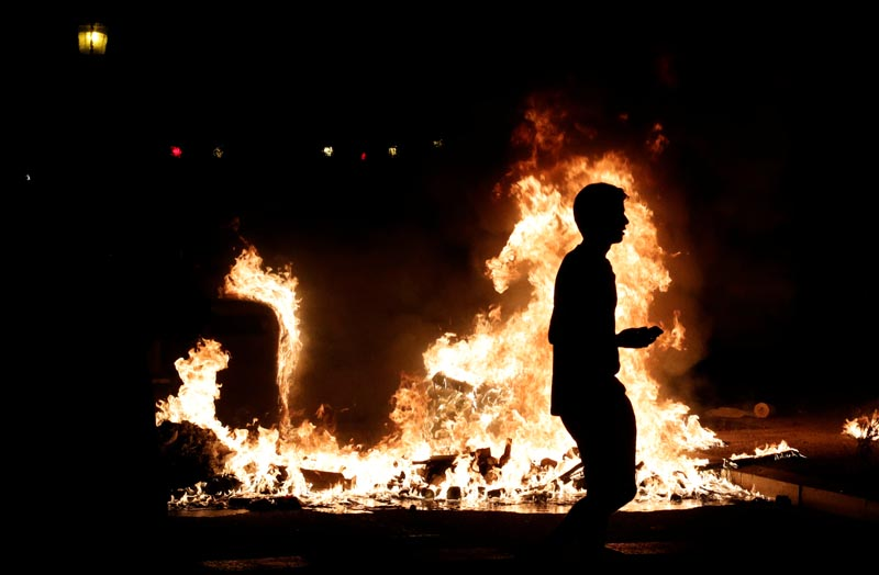 A demonstrators walks past a fire during protest after a verdict in a trial over a banned Catalonia's independence referendum in Barcelona, Spain, October 16, 2019. Photo: Reuters