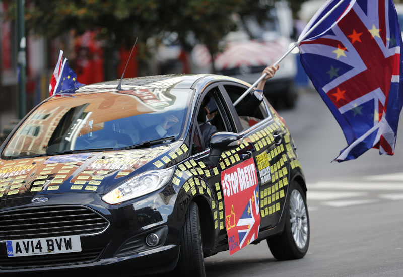 A man waves an EU and Union flag out of a car adorned with anti-Brexit decals in front of EU headquarters in Brussels, Thursday, Oct 17, 2019. Photo: AP