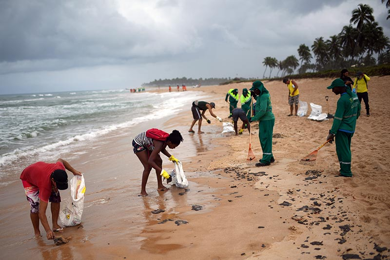 Municipal employees and residents work to remove an oil spill on Barra de Jacuipe beach in Camacari, Bahia state, Brazil October 22, 2019. Photo: Reuters