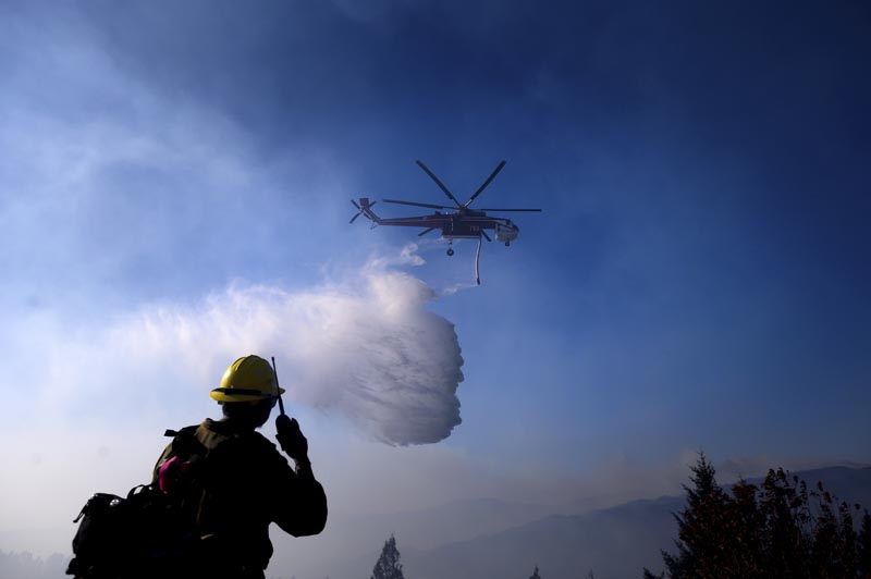 A helicopter drops water while battling the Kincade Fire near Healdsburg, California, on Tuesday, October 29, 2019. Photo: AP