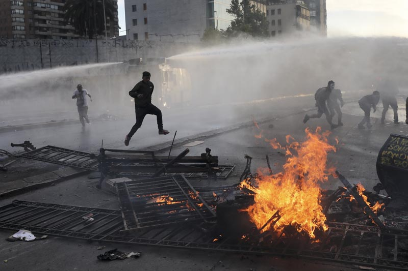 Anti-government protesters run from police spraying water cannons where a street barricade burns, set by demonstrators, in Santiago, Chile, Tuesday, October 29, 2019. Photo: AP