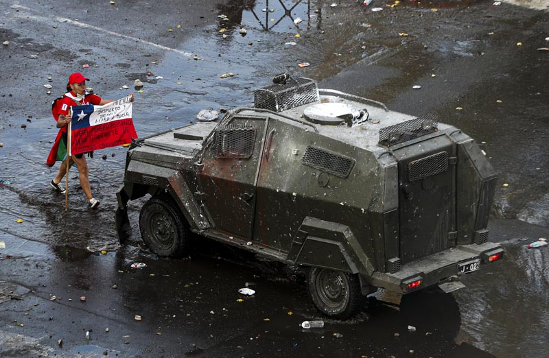 A demonstrator holds a Chilean flag toward an armored police vehicle during an anti-government march in Santiago, Chile, Tuesday, October 22, 2019. Photo: AP