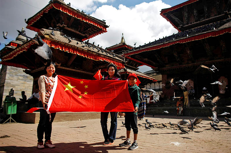 People display a Chinese flag as they pose during celebrations to mark the 70th founding anniversary of People's Republic of China, on its National Day, in Kathmandu, Nepal, October 1, 2019. Photo: Reuters