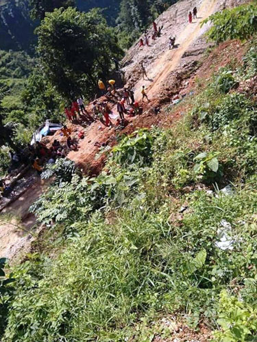 Locals are seen at the site where a bus (Ba 2 Kha 2715) -- en route to Kathmandu from Sipatar -- veered off the road, at Tikhukomod, in Indrawati Rural Municipaltity of Sindupalchok district, on Friday, October 11, 2019. Photo: RSS