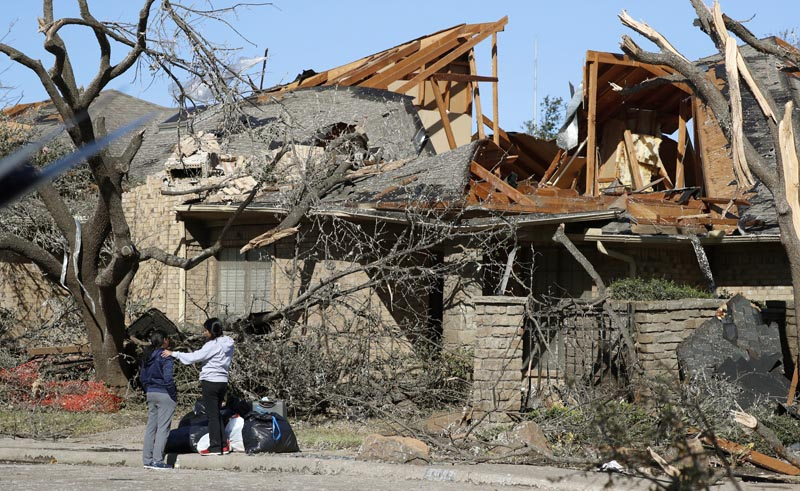 Women stand outside a house damaged by a tornado in the Preston Hollow section of Dallas, Monday, October 21, 2019. Photo: AP