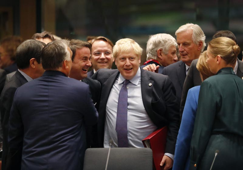 British Prime Minister Boris Johnson, center, is greeted by Luxembourg's Prime Minister Xavier Bettel, centre left, during a round table meeting at an EU summit in Brussels, Thursday, Oct. 17, 2019. Britain and the European Union reached a new tentative Brexit deal on Thursday, hoping to finally escape the acrimony, divisions and frustration of their three-year divorce battle. Photo: AP