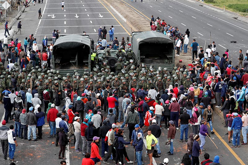 People surround soldiers as they block a road during protests after Ecuador's President Lenin Moreno's government ended four-decade-old fuel subsidies, in Lasso, Ecuador, on October 6, 2019. Photo: Reuters