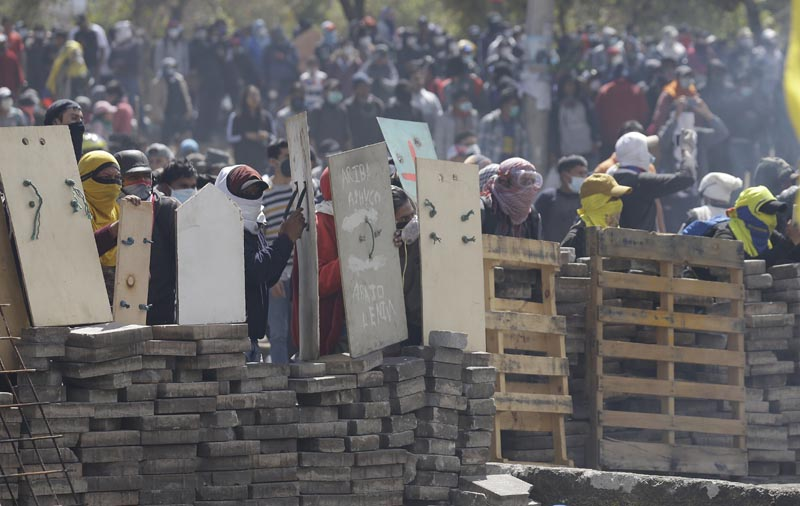 Anti-government demonstrators takes cover behind a barricade during clashes with police in Quito, Ecuador, Saturday, October 12, 2019. Photo: AP