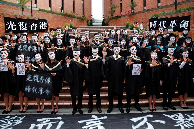 University students wearing Guy Fawkes masks pose for a photoshoot of a graduation ceremony to support anti-government protests at the Hong Kong Polytechnic University, in Hong Kong, China October 30, 2019. Photos: Reuters