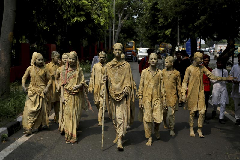 School children dressed as statues, depicting Indian freedom leader Mahatma Gandhi's Dandi March, cross a road to perform at a traffic intersection on the eve of Gandhi's 150th birth anniversary in New Delhi, India, Tuesday, Oct 1, 2019. Photo: AP