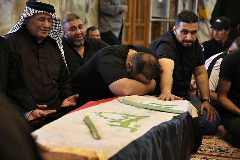 Mourners pray over the flag-draped coffin of a protester killed during anti-government protesters during his funeral at the Imam Ali shrine in Najaf, Iraq, Saturday, Oct 5, 2019. Photo: AP