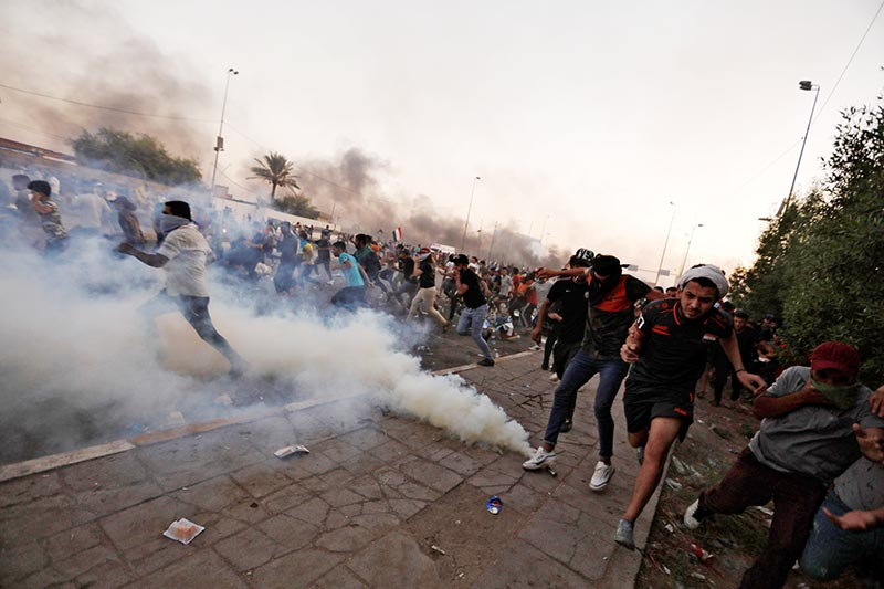 Demonstrators run as Iraqi security forces use tear gas during a protest after lifting of the curfew, following four days of nationwide anti-government protests turned violent, in Baghdad, Iraq, on October 5, 2019. Photo: Reuters