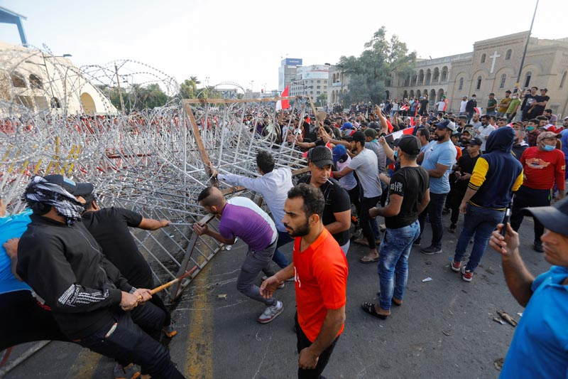 Demonstrators try to remove the fence during a protest over corruption, lack of jobs, and poor services, in Baghdad, Iraq October 25, 2019. Photo: Reuters