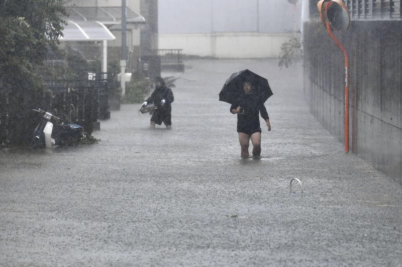 People walk through a flooded street affected by Typhoon Hagibis, in Shizuoka, central Japan Saturday, October 12, 2019. Photo: Kyodo News via AP