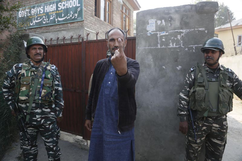 A Kashmiri village council candidate Ghulam Hassan Rather shows the indelible ink mark on his finger after casting his vote, outside a polling station on the outskirts of Srinagar, Indian-controlled Kashmir, Thursday, October 24, 2019. Photo: AP