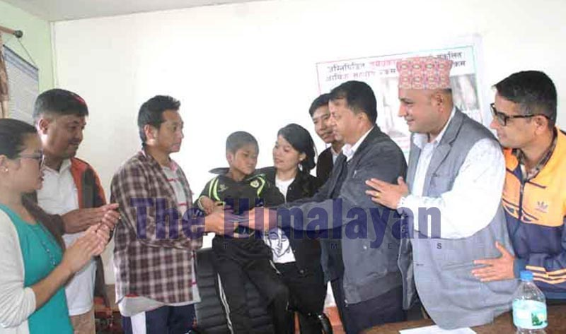 Chief District Officer Bishnu Hari Upadhaya (third from left) handing over the collected amount to Surya Prakash Raiu2019s father after Suryau2019s left foot was burnt  two months ago, in District Hospital, Khotang, on Tuesday, October 1, 2019. Photo: THT