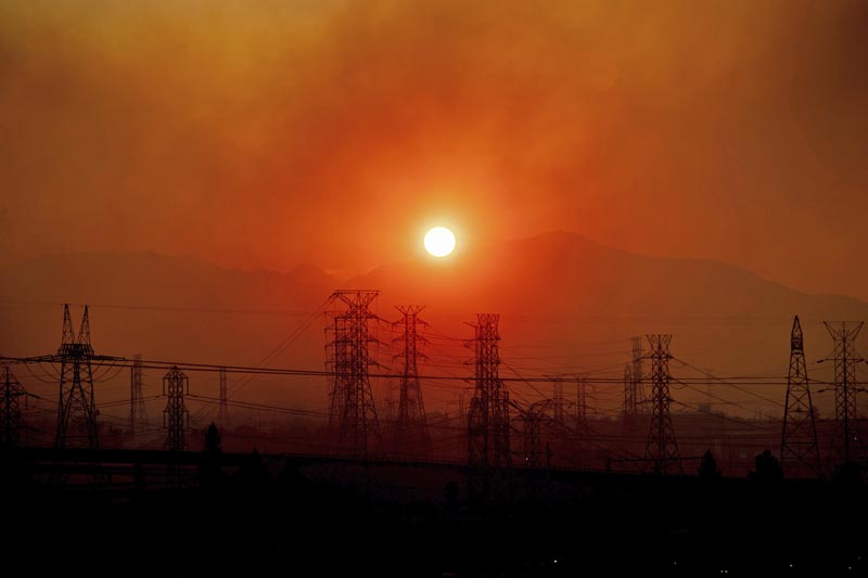 FILE - In this Friday, October 11, 2019, file photo, smoke from a wildfire called the Saddle Ridge Fire hangs above power lines as the sun rises in Newhall, California. Photo: AP