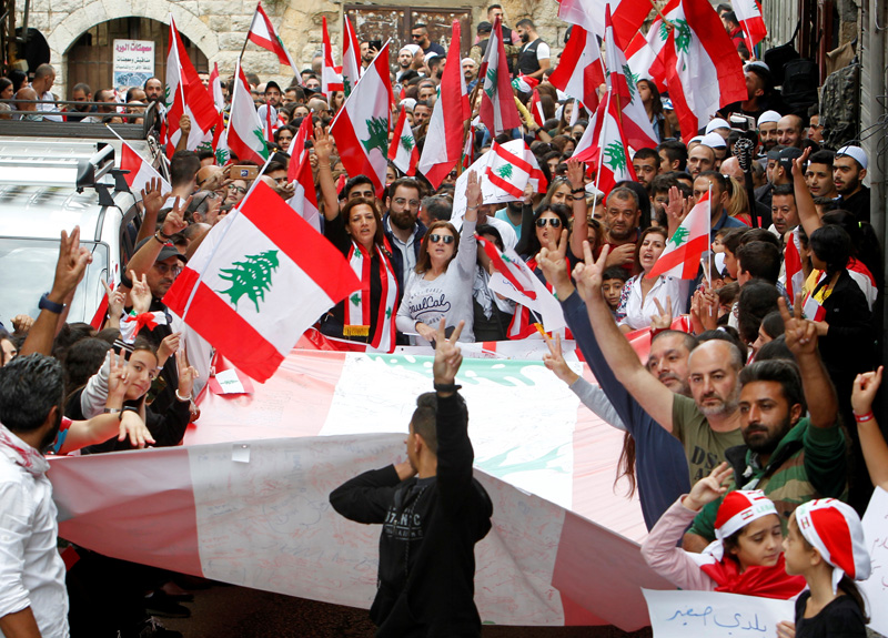 Demonstrators carry Lebanese flags during an anti-government protest in the mainly Druze town of Hasbaya, Lebanon October 25, 2019. Photo: Reuters