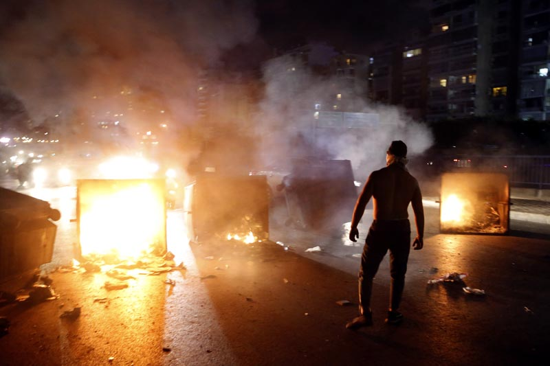 A supporter of Lebanese Prime Minister Saad Hariri burns garbage containers to block  a main road, in Beirut, Lebanon, Tuesday, October 29, 2019. Photo: AP