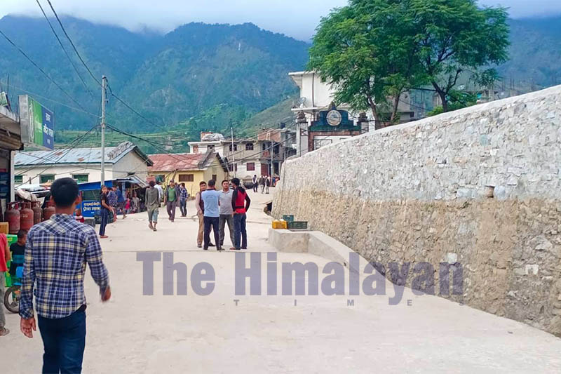 Commuters are seen walking along the road in Martardi, district headquaters of Bajura, on Monday, October 14, 2019. Photo: Prakash Singh/THT