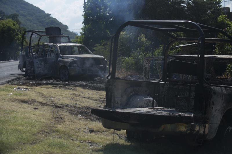 Charred trucks that belong to the Michoacan state police stand on the roadside after they were attacked in El Aguaje, Mexico, Monday, October 14, 2019. Photo: AP