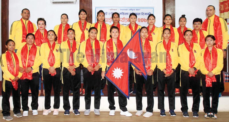 Skipper Aruna Shahi holds the national flag as she poses for the group photo with her team members and officials at a farewell programme, in Kathmandu on Tuesday. Photo: THT