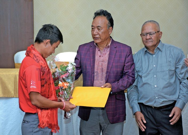 NGA President Tashi Ghale honouring golfer Sukra Bahadur Rai as Kathmandu District Golf Association President Madan Rana looks on during a programme in Kathmandu on Monday, October 21, 2019. Photo: Naresh Shrestha / THT