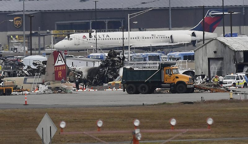 A Delta commercial airline plane taxis to take-off behind investigators at the wreckage of World War II-era bomber plane that crashed at Bradley International Airport in Windsor Locks, Description Connecticut Wednesday, October 2, 2019. Photo: AP