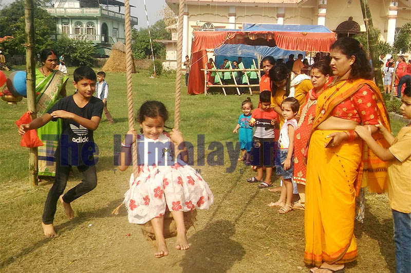 A little girl plays swing as others look on in the premises of Durga temple at Anchalpur in Bhairahawa, on Wednesday, October 16, 2019. Photo: Krishna Prasad Dhakal/THT