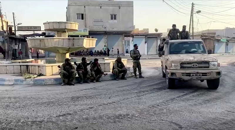 Armed rebel soldiers are seen on the street of Tal Abyad, Syria October 13, 2019, in this screen grab taken from video. Photo: Reuters TV via Reuters