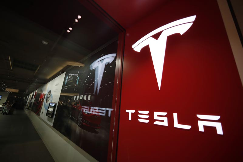 FILE- In this February 9, 2019, file photo, a sign bearing the company logo is displayed outside a Tesla store in Cherry Creek Mall in Denver. Photo: AP
