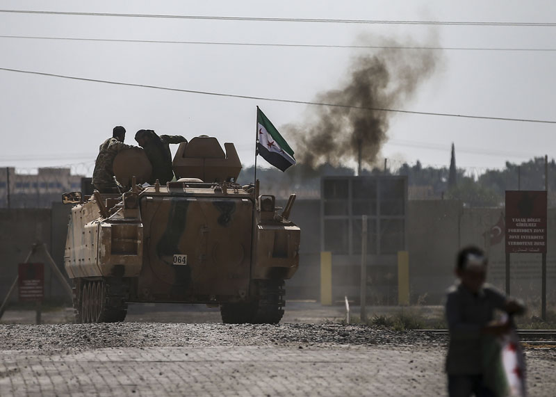 Turkish-backed Syrian opposition fighters on an armoured personnel carrier drive to cross the border into Syria, in Akcakale, Sanliurfa province, southeastern Turkey, Friday, Oct 18, 2019. Photo: AP