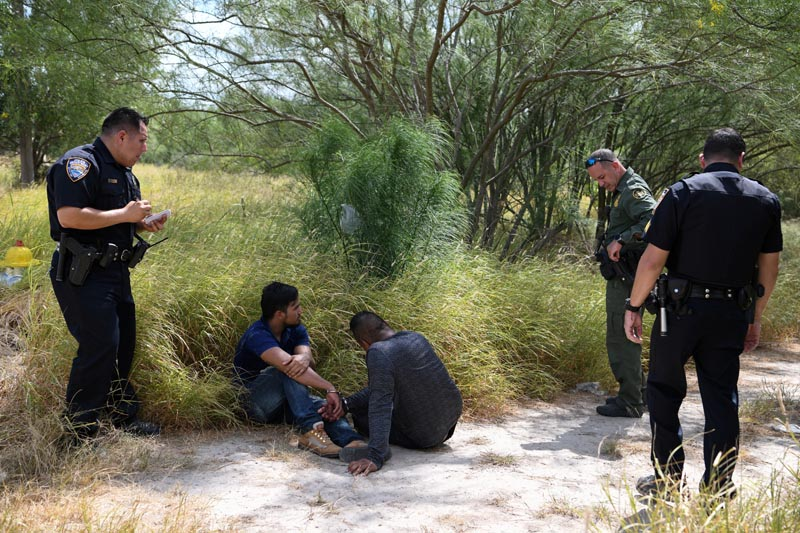 FILE - Migrant men sit on the ground after being detained by law enforcement for illegally crossing the Rio Grande and attempting to evade capture in Hidalgo, Texas, US, August 23, 2019. Photo: Reuters