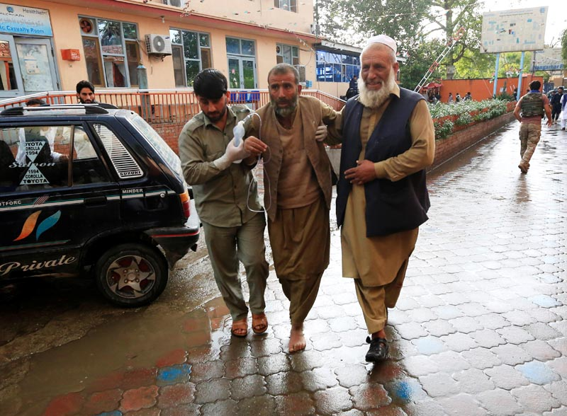 Men carry an injured person to a hospital after a bomb blast at a mosque, in Jalalabad, Afghanistan October 18, 2019. Photo: Reuters