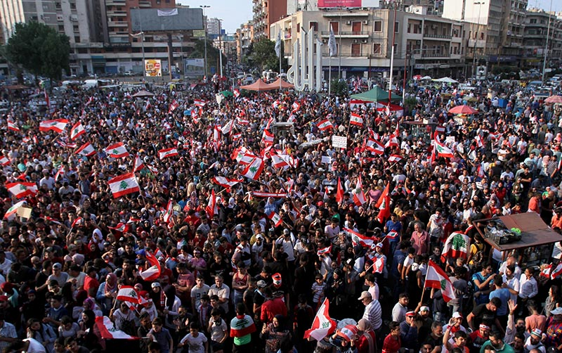 Demonstrators carry national flags during an anti-government protest in Tripoli, Lebanon October 22, 2019. Photo: Reuters