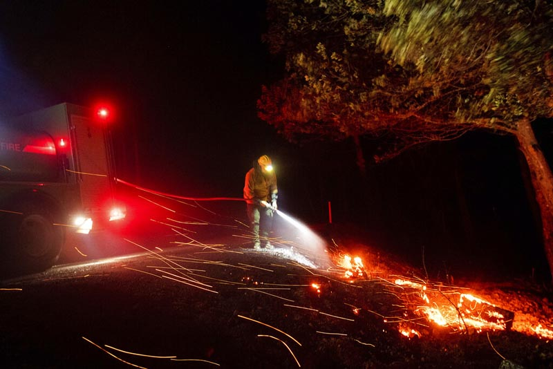 A firefighter battling the Kincade fire extinguishes a hot spot as strong winds send embers flying in Calistoga, California, on Tuesday, October 29, 2019. Photo: AP