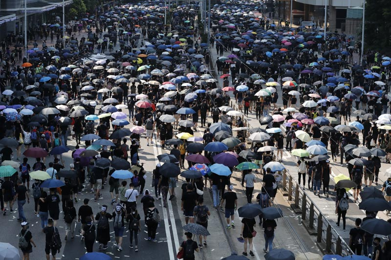 Anti-government protesters holding umbrellas march past police headquarters in Hong Kong, Tuesday, October 1, 2019. Photo: AP