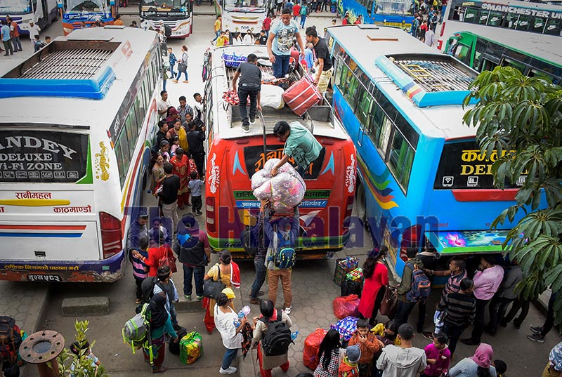 People preparing to board passenger buses to head for their homes to celebrate Dashain, in New Bus Park, Kathmnadu, on Wednesday. Photo: Naresh Shrestha/ THT