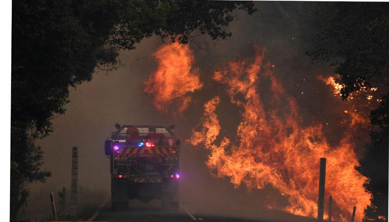 A fire truck is seen near a bushfire in Nana Glen, near Coffs Harbour, Australia, November 12, 2019. Photo: Reuters